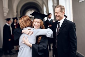 Parents hugging the daughter who just graduated from college
